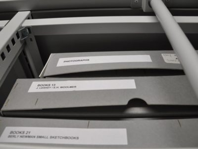 Image of three grey boxes, the top one inscribed with 'Photographs' in RAMM's storage space for museum objects