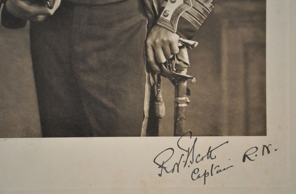 Detail of signature 'R.F. Scott, Captain R.N.' underneath a black-and-white photograph showing Captain Robert Falcon Scott