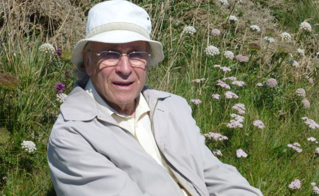 Photograph of butterfly collector Derrick Worton sat surrounded by wildflowers
