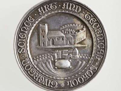 Photograph of a silver 'Hadow Medal' from a school in Tiverton. It depicts images of the town with its river, church and castle. Around the edge is the inscription 'TIVERTON SCIENCE ART AND TECHNICAL SCHOOL'.