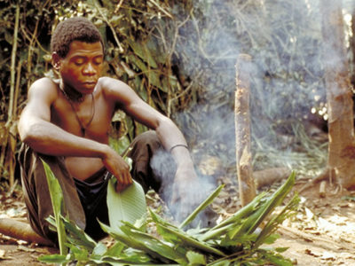 A Baka man seated by a campfire