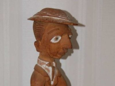 A wooden carving of a colonial officer