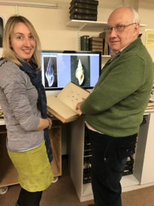 Two people stood in front of a computer. Graham Oliver is holing a large old book open at an illustration of shells. Two photographs of shells are displayed on the computer behind them. They correspond to the image in the book.