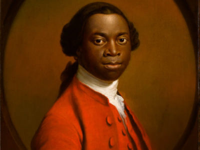 A black man in eighteenth century clothing and wig faces us, head and shoulders showing. His body is at an angle. The image is an oval shape, and the man is wearing a red jacket and white stock